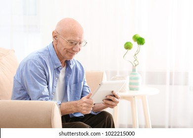 Hearing impaired man with tablet at home
