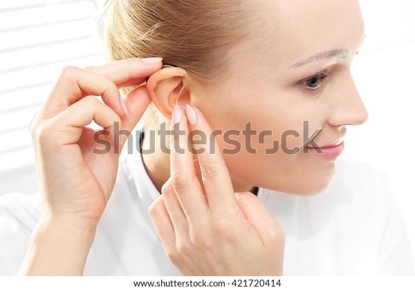 Hörstörungen. Junge Frau nimmt Hörgerät an
