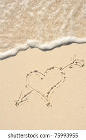 Heart with an Arrow Drawn in the Sand on a Beach