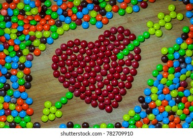 Heart and arrow made out of round colorful chocolate candy