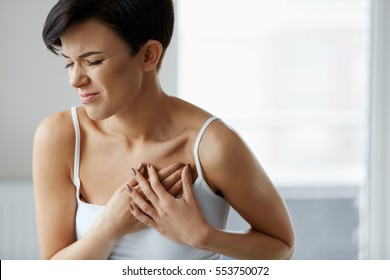 Heart Attack. Beautiful Young Woman Feeling Sharp Strong Pain In Chest. Portrait Of Attractive Female Having Heart Attack, Holding Hand On Painful Chest. Health Care, Medical Concept. High Resolution