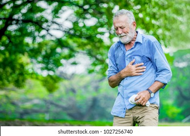 Heart attack concept. Senior man suffering from chest pain outdoor in park,