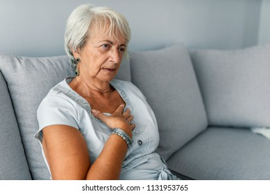 Heart attack concept. Woman suffering from chest pain, Health care. Severe heartache, Having heart attack or Painful cramps, Pressing on chest with painful expression.