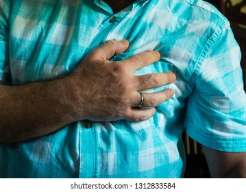 Heart attack. Man's hand on his chest
