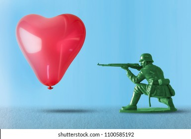 Heart balloon floating as a target for a toy soldier with gun representing the negative impact of war and the destruction of the flow of love with gun crime