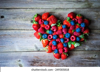 Heart of berries on wooden background