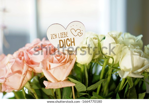 a heart between a lot of roses with an inscription: i love you