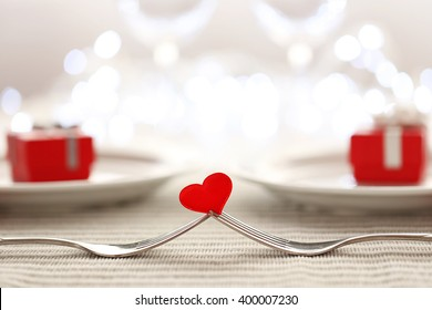 Heart between two forks on a table set for two, close up