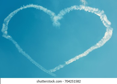 A heart in the blue sky from skywriting planes at an air show. Symbol of love in the heaven. Trail of an airplane in the form of a big heart.