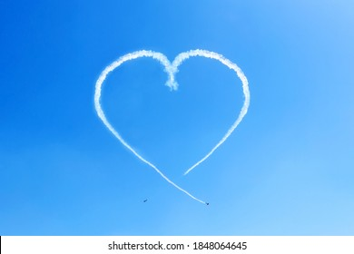 Heart in the blue sky from two skywriting small planes at an air show. Symbol of love in the heaven