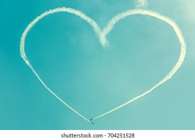 A heart in the blue sky from two skywriting small planes at an air show. Symbol of love in the heaven. Trail of an airplane in the shape of a big heart.