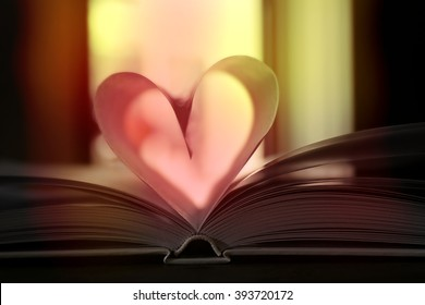 Heart from book pages on dark blurred background