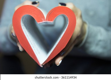 Heart from book pages with red edges