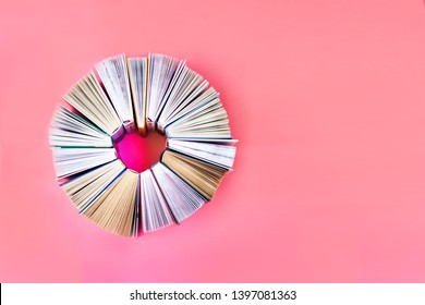 The heart of books on coral background. Top view. Love story books. Copy space
