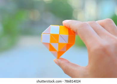 A heart by yellow,white magic snake ruler twisty toy puzzle in a man hand with blurred green nature background.It can let children show unlimited imagination by rotate the magic cube,learning concept.