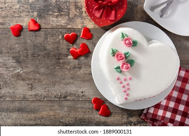 Heart cake for St. Valentine's Day, Mother's Day, or Birthday, decorated with roses and pink sugar hearts on wooden table