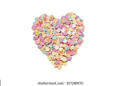 Heart candies arranged in a heart shape on a white background