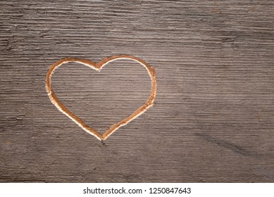 Heart carved on the wooden plank.  Cuttings from wood.  Valentine's Day. A symbol of love. A pattern on the tree.