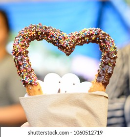 Heart churros dipped with chocolate sauce and sprinkles rainbow contrast with blue sky background