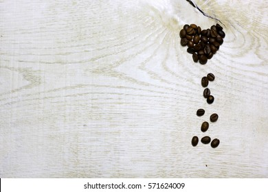 Heart of coffee beans on light wooden background. Love card for Valentine's day. Concept with big copyspase for cafe or bistro advert banner.