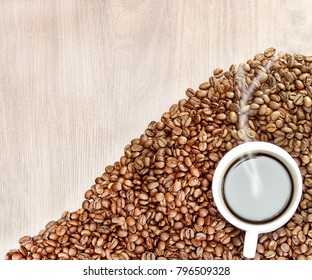 the heart of coffee beans on a wooden background in the center of a cup of white with coffee, with it comes steam