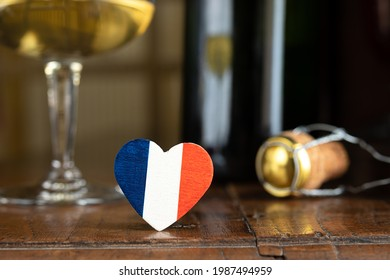 A heart in the colors of the French flag, a glass and a french champagne bottle cork in the background, on the dark old table, Bastille Day and French National Day concept