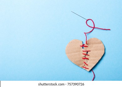 The heart is combined, love is back. A paper heart made of two halves is sewn with a red thread with needleon a blue background