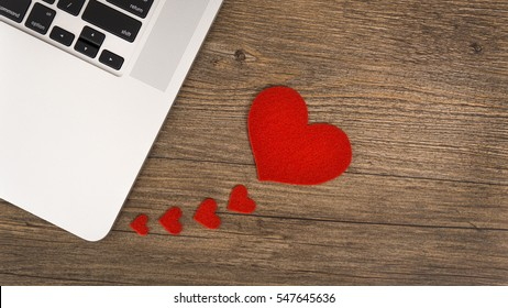 A heart connected with computers. Hearts on the wooden background.
