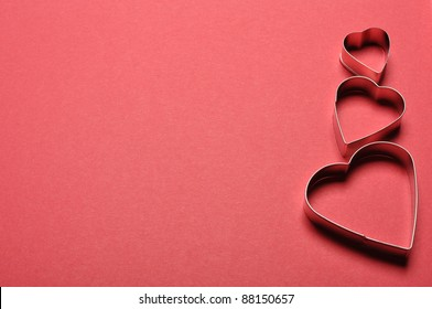 Heart cookie cutter on a sheet of textured red paper