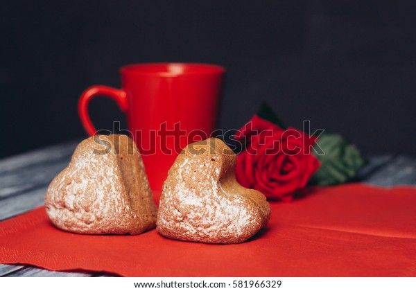 heart cookies on a red napkin, a red circle and a red rose.