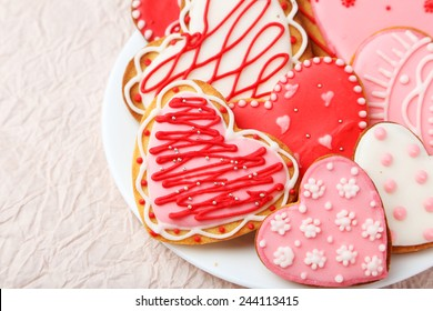 Heart cookies on white plate on pink paper background