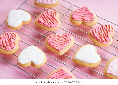 Heart cookies with sweet pink icing on baking rack, love concept.