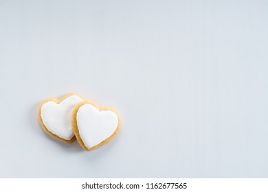 Heart cookies with sweet white icing on white background, top view. love concept.