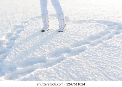 Heart in deep snow created by footsteps. Concept of love. Woman legs dressed in warm snow boots. Winter nature background.
