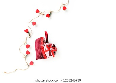 Heart from different patches of cloth fabric on a white background. Clothespins with red hearts from wood are strung on a string. Mother's day, Valentine's day, wedding day - concept. Copy space.