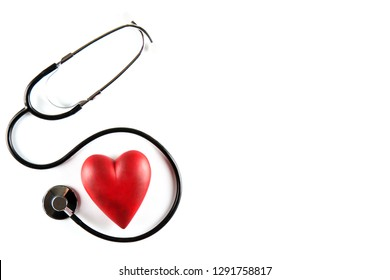 Heart disease awareness and prevention concept. Stethoscope and red heart on white isolated background with a lot of copy space for text. Close up, top view. Medical equipment for cardiologist.
