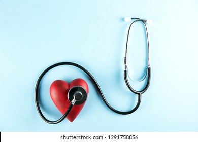 Heart disease awareness and prevention concept. Stethoscope and red heart on pale blue isolated background with a lot of copy space for text. Close up, top view. Medical equipment for cardiologist.