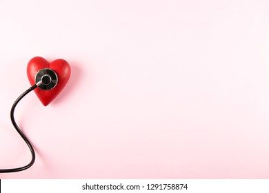 Heart disease awareness and prevention concept. Stethoscope and red heart on pale pink isolated background with a lot of copy space for text. Close up, top view. Medical equipment for cardiologist.