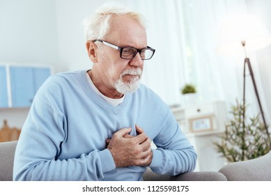 Heart disease symptoms. Attentive senior man touching chest and wearing glasses