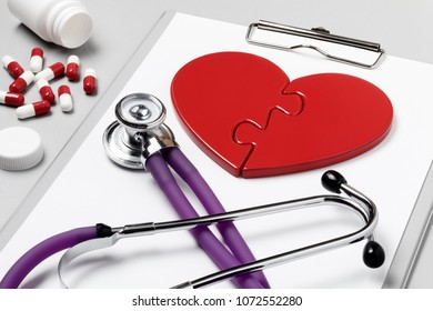 Heart Doctor's Accessories. Close-up composition of traditional symbol of a human heart surrounded by the medical requisite of therapist: stethoscope, writing tablet and medical pills.