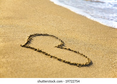 """""""Heart"""" drawing at sand, with sea wave"""