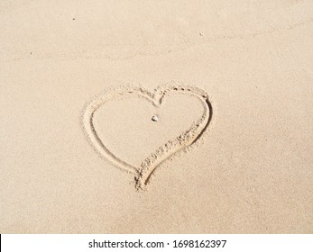 Heart drawn by finger on yellow sand, close up view. Photographed in egyptian beach in february. Yellow sand background