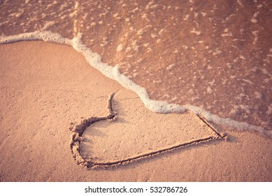 Heart drawn on the beach sand being washed away by a wave. Toasted sand tone. Love affair, summer love or breakup and divorce concept. Ephemeral romantic love. Not true love. End of relationship.