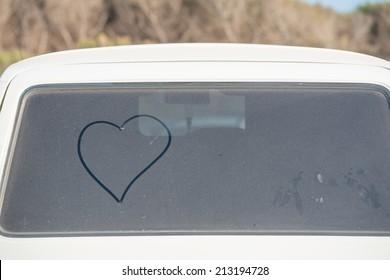 heart drawn on a dirty back window