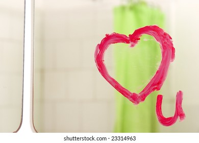 a heart drawn on a mirror with lipstick