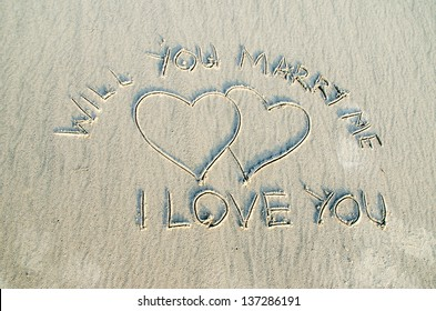 Heart drawn on sand with I love you and will you marry me text on it