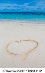 Heart drawn on the sand of a sea beach on a tropical island by the ocean