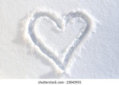 Heart drawn on white-blue snow