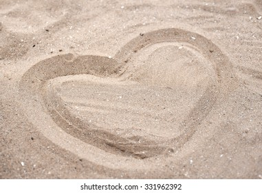 Heart drawn in the sand. Beach background.