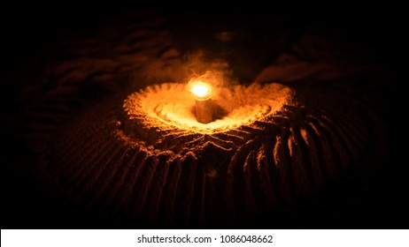 Heart  drawn in the sand with candlelight. Candlelight background. Romantic candlelight heart on the beach. Candle light dinner on the beach